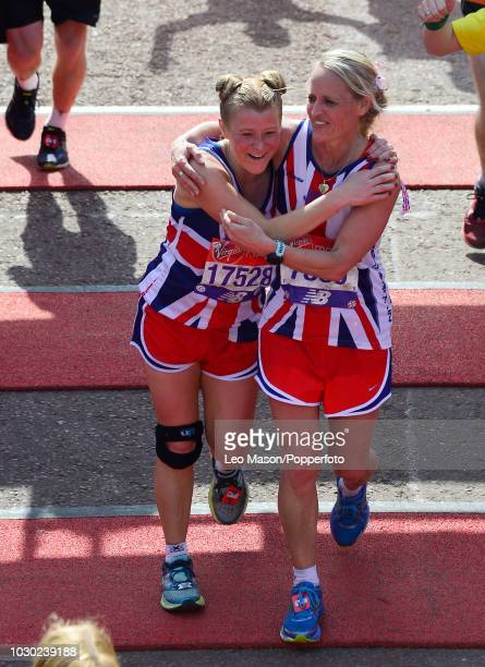 Runners wearing Union Flag shirts embrace at the finish on The Mall during The Virgin London Marathon on April 22 2018 in London England