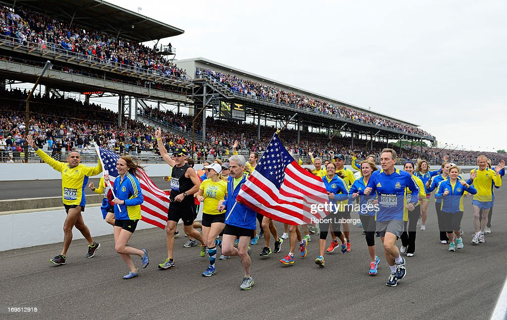 Runners who participated in the 2013 Boston Marathon run down pit road during the IZOD IndyCar Series 97th running of the Indianpolis 500 mile race at the Indianapolis Motor Speedway on May 26, 2013 in Indianapolis, Indiana.