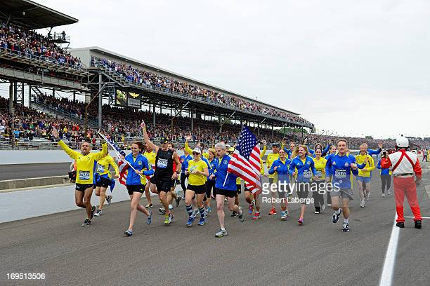 Runners who participated in the 2013 Boston Marathon run down pit road during the IZOD IndyCar Series 97th running of the Indianpolis 500 mile race...