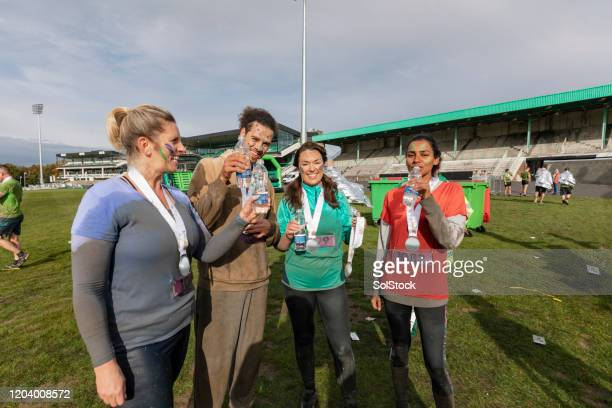 runners with medals drinking water in sports field after race - medallist stock pictures, royalty-free photos & images