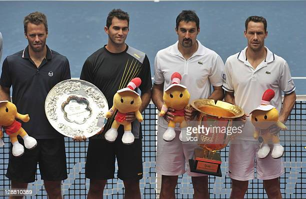 Runners-up Robert Lindstedt of Sweden and Horia Tecau of Romania poses with winners Nenad Zimonjic of Serbia and Michael Llodra of France after the...