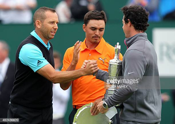 Runnersup Spain's Sergio Garcia and US golfer Rickie Fowler congratulate Northern Ireland's Rory McIlroy after finishing two strokes behind winner at...