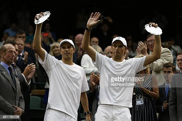 Runnersup US players Bob and Mike Bryan hold their trophies after losing their men's doubles final match to Canada's Vasek Pospisil and US player...
