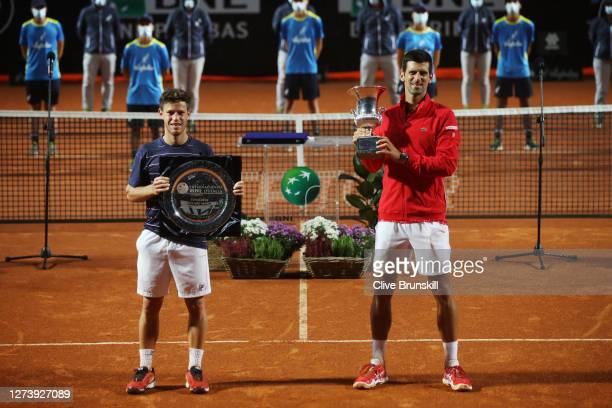 Runner-up Diego Schwartzman of Argentina and winner Novak Djokovic of Serbia pose with their respective trophies after their men's final match during...