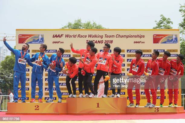 Runner-up team Italy, winner team Japan and third place team China take a selfie during medal ceremony of Men's 20 kilometres Race Walk of IAAF World...