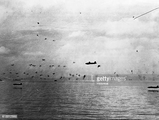 Running a gauntlet of anti-aircraft fire, four Japanese Betty medium bombers come in low at Guadalcanal Island to attack U.S. Transports, extreme...