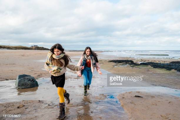 running along the beach - moving after stock pictures, royalty-free photos & images