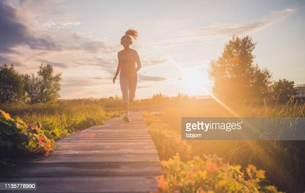 running at sunset in public park. - extra long stock pictures, royalty-free photos & images