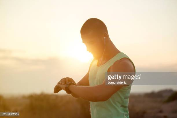 running athlete man looking at smartwatch - heart health stock pictures, royalty-free photos & images