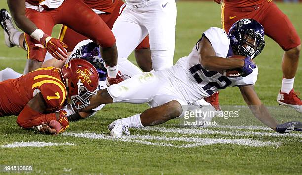 Running back Aaron Green of the TCU Horned Frogs dives for yards as he is tackled by defensive back Qujuan Floyd of the Iowa State Cyclones in the...