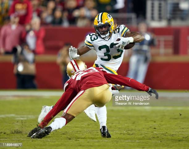 Running back Aaron Jones of the Green Bay Packers carries the ball as cornerback Ahkello Witherspoon of the San Francisco 49ers defends during the...