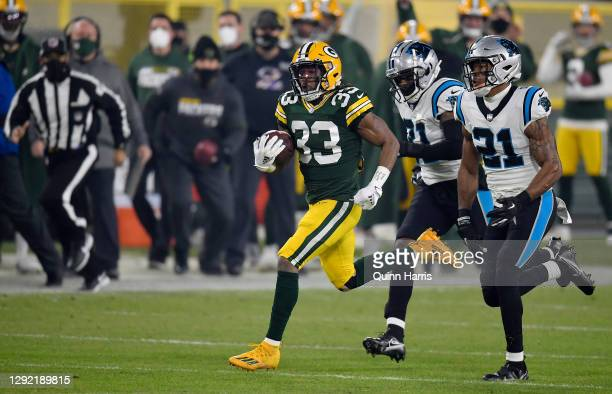 Running back Aaron Jones of the Green Bay Packers carries the ball for first down against outside linebacker Jeremy Chinn of the Carolina Panthers in...