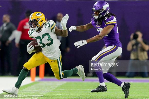 Running back Aaron Jones of the Green Bay Packers is forced out of bounds by the defense of the Minnesota Vikings at U.S. Bank Stadium on December...