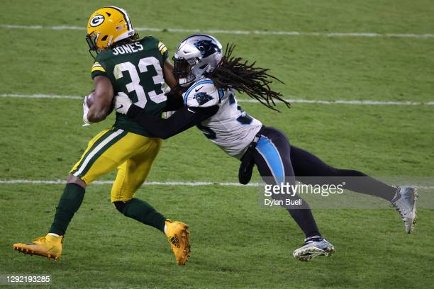 Running back Aaron Jones of the Green Bay Packers is tackled by free safety Tre Boston of the Carolina Panthers during the game at Lambeau Field on...