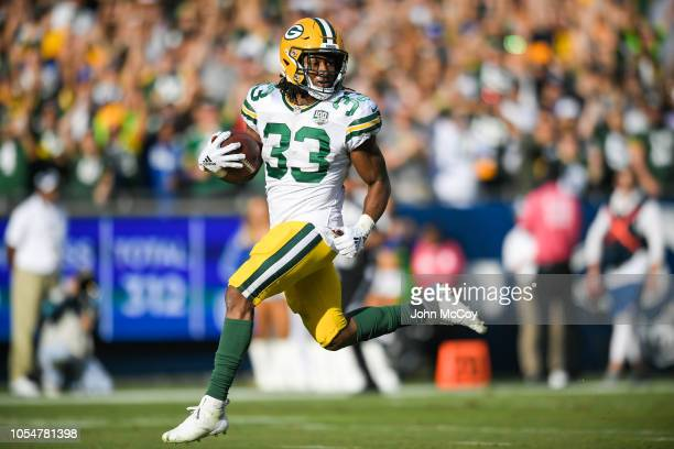 Running back Aaron Jones of the Green Bay Packers looks back as he steps into the end zone for a touchdown in the third quarter against the Los...