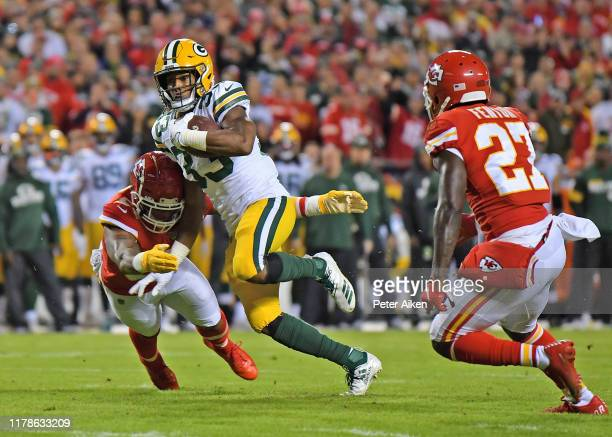 Running back Aaron Jones of the Green Bay Packers rushes between Kansas City Chiefs defenders during the second half at Arrowhead Stadium on October...