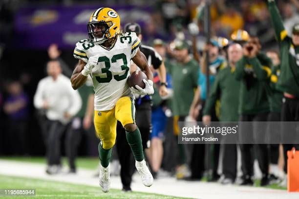 Running back Aaron Jones of the Green Bay Packers rushes for a touchdown in the third quarter of the game against the Minnesota Vikings at US Bank...