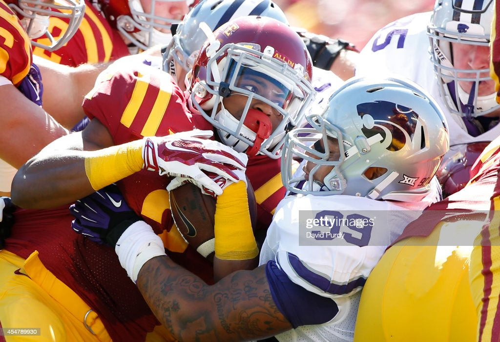 Running back Aaron Wimberly #2 of the Iowa State Cyclones is tackled by defensive tackle Valentino Coleman #99 of the Kansas State Wildcats in the first half of play at Jack Trice Stadium on September 6, 2014 in Ames, Iowa.