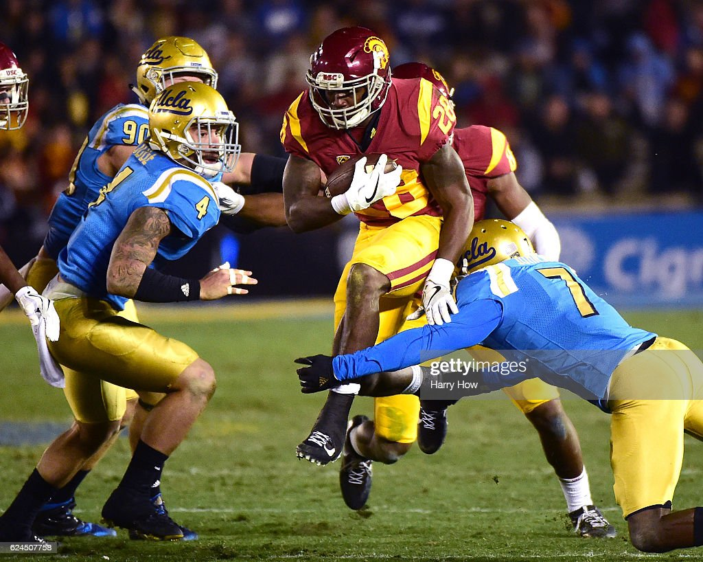 Running back Aca'Cedric Ware #28 of the USC Trojans jumps to avoid a tackle from defensive back John Johnson #7 and linebacker Cameron Judge #4 of the UCLA Bruins during a 36-14 Trojan win at Rose Bowl on November 19, 2016 in Pasadena, California.