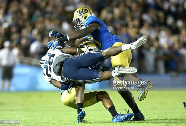 Running back Adam Hine of the BYU Cougars is tackled by linebacker Myles Jack and defensive back Marcus Rios of the UCLA Bruins at the Rose Bowl on...