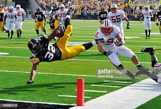Running back Adam Robinson of the University of Iowa Hawkeyes is knocked down at the one yard line by line backer Blake Sorensen of the Wisconsin...