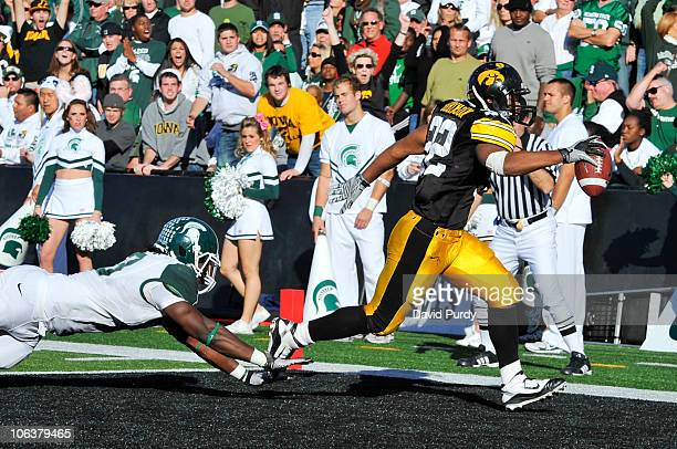 Running back Adam Robinson of the University of Iowa Hawkeyes runs the ball into the end zone for a touchdown as line backer Greg Jones of the...