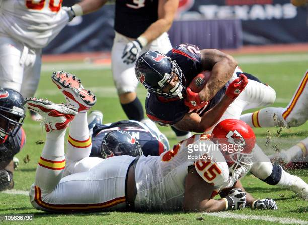 Running back Adrian Foster of the Houston Texans dives in for a touchdown over defensive tackle Ron Edwards of the Kasnsas City Chiefs at Reliant...