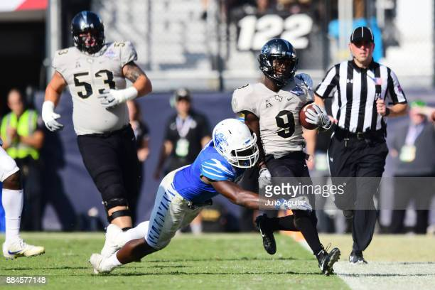 Running back Adrian Killins Jr #9 of the UCF Knights gets a big first down in the third quarter of the ACC Championship against the Memphis Tigers at...
