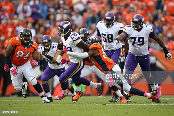 Running back Adrian Peterson of the Minnesota Vikings carries the ball as inside linebacker Brandon Marshall of the Denver Broncos hangs on for the...