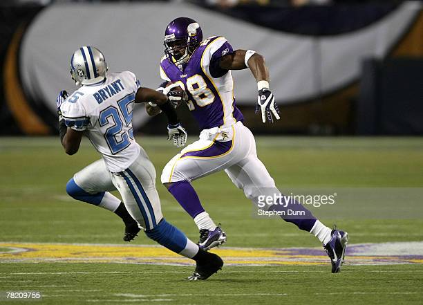 Running back Adrian Peterson of the Minnesota Vikings carries the ball as cornerback Fernando Bryant of the Detroit Lions defends on December 2 2007...