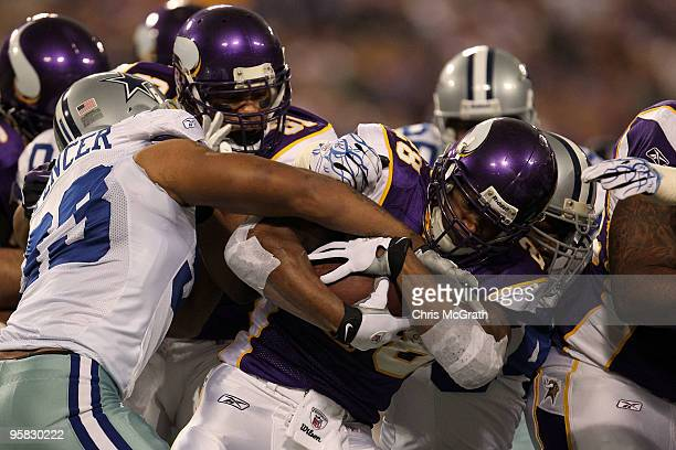 Running back Adrian Peterson of the Minnesota Vikings fights to hold onto the ball against Anthony Spencer of the Dallas Cowboys during the first...