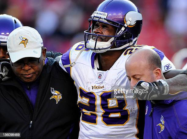 Running back Adrian Peterson of the Minnesota Vikings is helped off the field after being injured in the third quarter against the Washington...