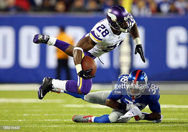 Running back Adrian Peterson of the Minnesota Vikings is tackled by cornerback Trumaine McBride of the New York Giants during a game at MetLife...