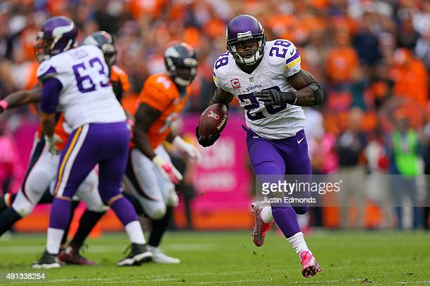 Running back Adrian Peterson of the Minnesota Vikings rushes for a 48 yard touchdown against the Denver Broncos in the fourth quarter of a game at...