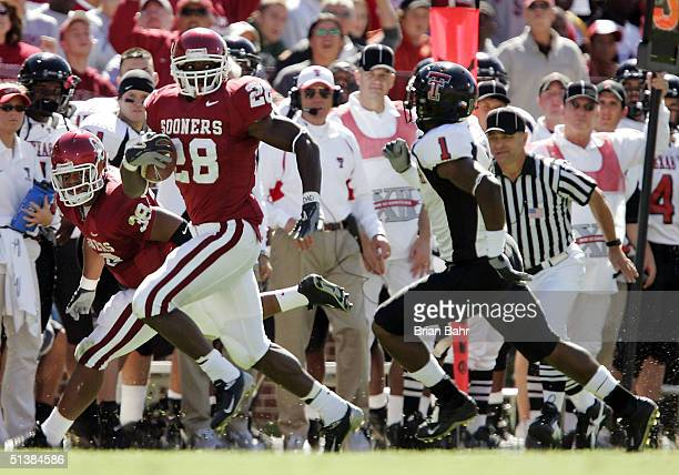 Running back Adrian Peterson of the Oklahoma Sooners leads safety Vincent Meeks of the Texas Tech Red Raiders on a 64-yard run to set up a touchdown...