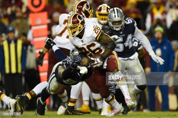 Running back Adrian Peterson of the Washington Redskins breaks the tackle of defensive tackle David Irving of the Dallas Cowboys in the fourth...