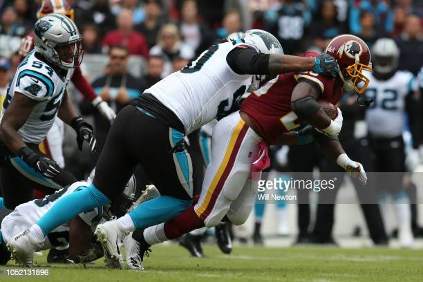 Running back Adrian Peterson of the Washington Redskins is tackled as he carries the ball in the first quarter against the Carolina Panthers at...