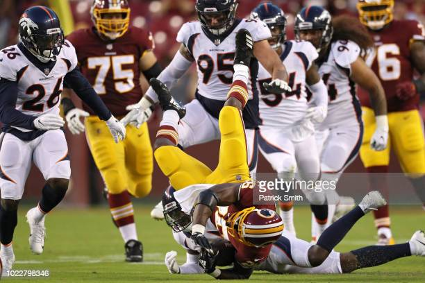 Running back Adrian Peterson of the Washington Redskins is tackled by defensive back Tramaine Brock of the Denver Broncos in the first quarter during...