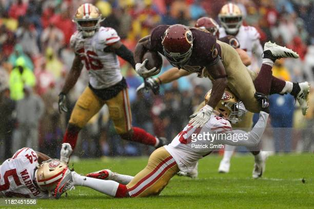 Running back Adrian Peterson of the Washington Redskins is tackled by cornerback Jimmie Ward of the San Francisco 49ers during the first half at...