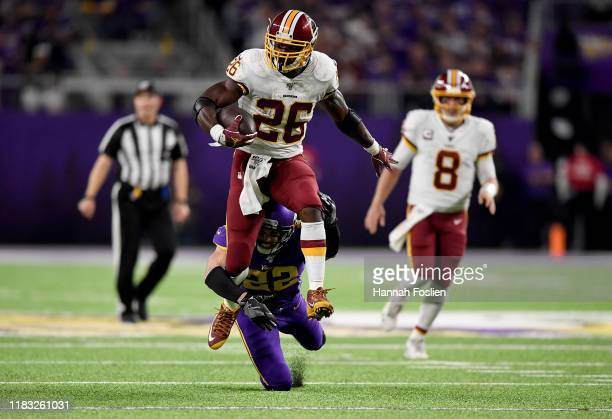 Running back Adrian Peterson of the Washington Redskins is tackled by Harrison Smith of the Minnesota Vikings during the game at US Bank Stadium on...
