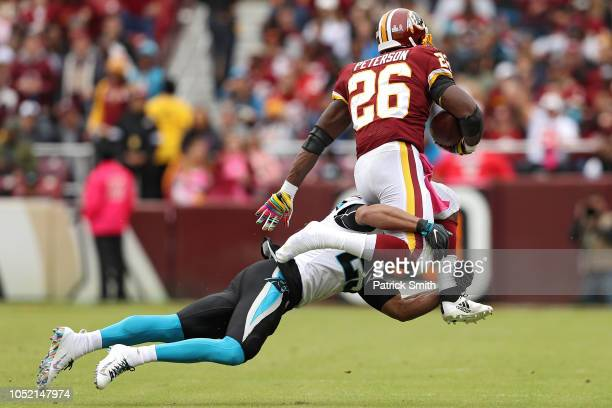 Running back Adrian Peterson of the Washington Redskins loses his shoe as he rushes past strong safety Eric Reid of the Carolina Panthers during the...