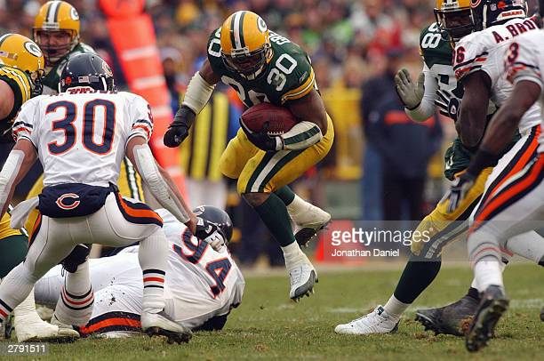 Running back Ahman Green of the Green Bay Packers hops through the line as safety Mike Brown of the Chicago Bears prepares to make the tackle during...