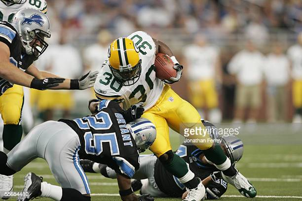Running back Ahman Green of the Green Bay Packers is tackled by Fernando Bryant of the Detroit Lions during the NFL game on September 11 2005 at Ford...