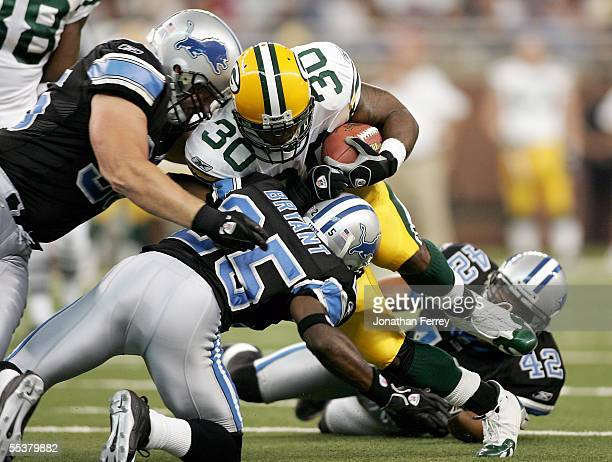 Running back Ahman Green of the Green Bay Packers is tackled by cornerbacks Fernando Bryant and Andre Goodman of the Detroit Lions on September 11...