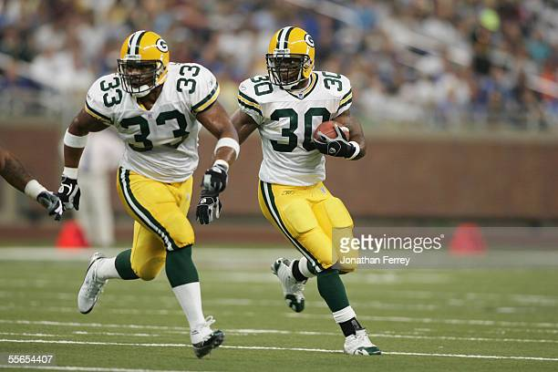 Running back Ahman Green of the Green Bay Packers runs the ball as teammate William Henderson blocks for him against the Detroit Lions during the NFL...