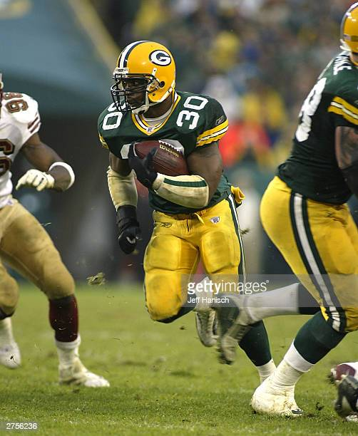 Running back Ahman Green of the Green Bay Packers rushes through a hole in the line against the San Francisco 49ers during the NFL game on November...