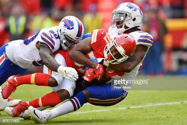 Running back Akeem Hunt of the Kansas City Chiefs is tackled by Ramon Humber and teammate defensive end Jerry Hughes of the Buffalo Bills during the...