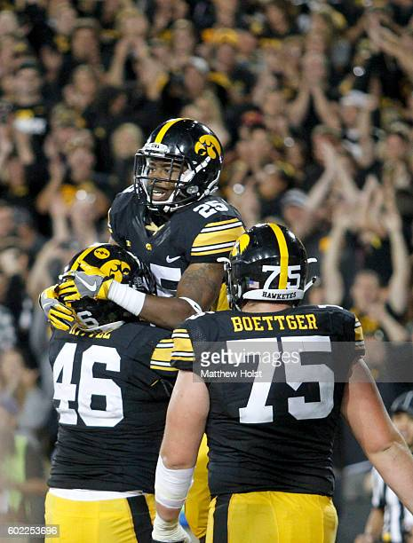 Running back Akrum Wadley of the Iowa Hawkeyes celebrates with tight end George Kittle after scoring a touchdown during the third quarter against the...