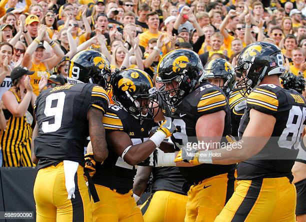 Running back Akrum Wadley of the Iowa Hawkeyes celebrates with wide receiver Jerminic Smith and offensive lineman Sean Welsh after scoring a...