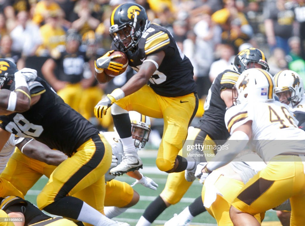 Running back Akrum Wadley #25 of the Iowa Hawkeyes leaps through a hole in the defensive line during the fourth quarter against the Wyoming Cowboys on September 2, 2017 at Kinnick Stadium in Iowa City, Iowa.